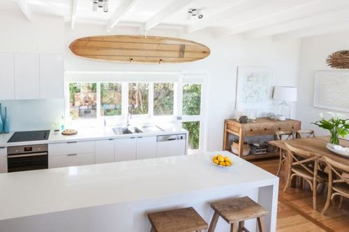 Bright coastal kitchen with sleek lines leading in a rustic beach style dining space
